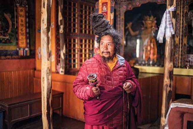 Dans un monastère, à Muktinath, Khenpo Tashi récite des mantras pendant qu'il fait tourner le moulin à prières.