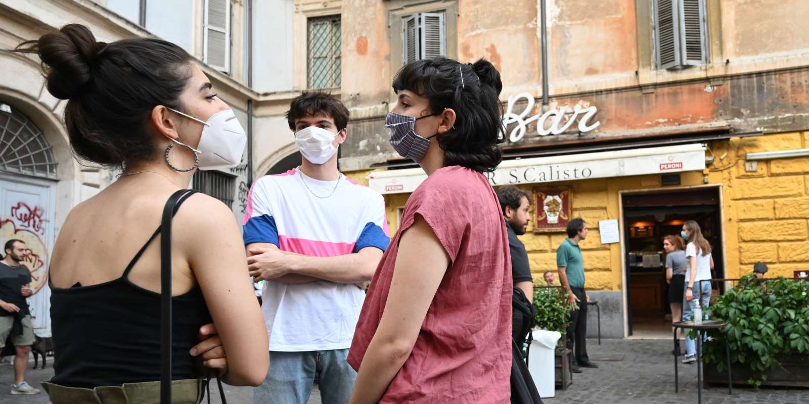 Youth gather for an aperitif drink outside a bar in the Trastevere district of Rome, on May 18, 2020 as the country's lockdown is easing after over two months, aimed at curbing the spread of the COVID-19 infection, caused by the novel coronavirus. Restaurants and churches reopen in Italy on May 18, 2020 as part of a fresh wave of lockdown easing in Europe and the country's latest step in a cautious, gradual return to normality, allowing businesses and churches to reopen after a two-month lockdown. / AFP / Alberto PIZZOLI