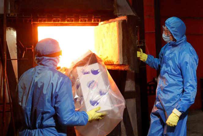 Des masques protecteurs et des gants usagés sont plongés dans un incinérateur, au milieu de l'épidémie due au coronavirus, à Kiev, le 19 mai.