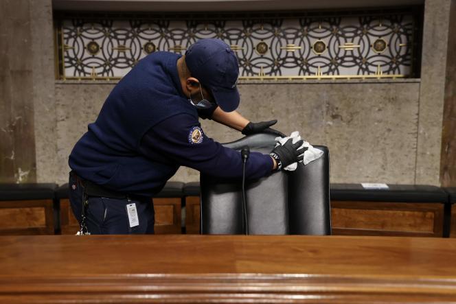 Un employé nettoie les chaises du Sénat entre chaque audience, le 6 mai à Washington.
