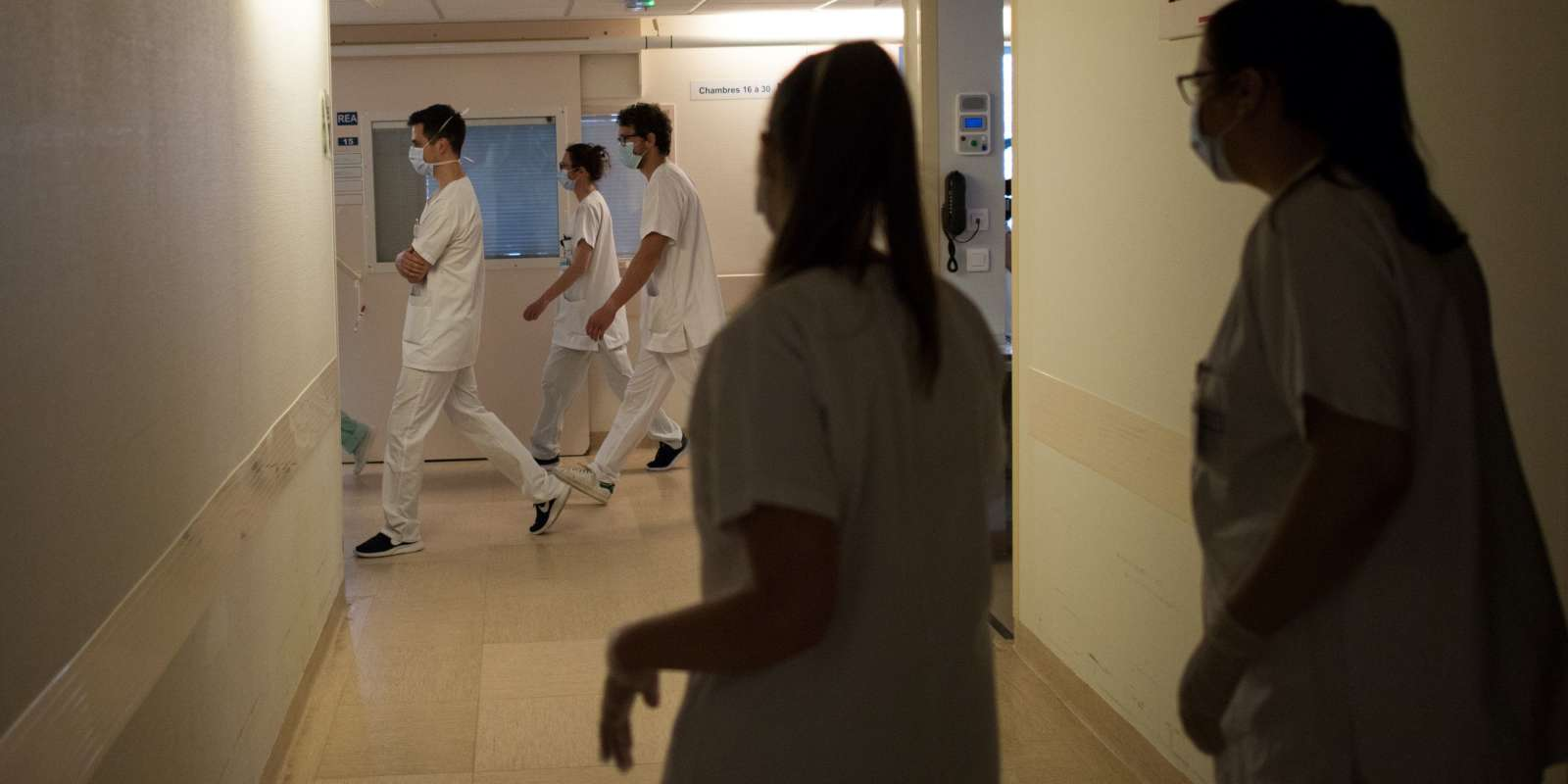 Caregivers walk down a corridor in the intensive care service of the Nantes university hospital, on May 19, 2020 in Nantes, western France, as France eased lockdown measures to curb the spread of the COVID-19 pandemic, caused by the novel coronavirus. / AFP / Loic VENANCE