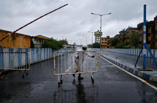 Avant l'arrivée du cyclone Amphan, le 20 mai, un policier ferme une route dangeureuse à Calcutta, en Inde.