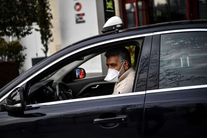 Un chauffeur de taxi attend des clients à l'extérieur dela gare d'Austerlitz, à Paris, le 17 mars.