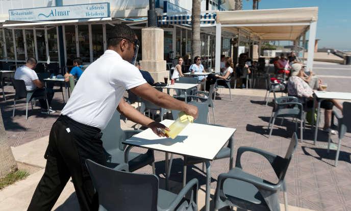 Un serveur désinfecte une table sur une terrasse de la plage de La Malvarrosa à Valence, le 19 mai 2020.