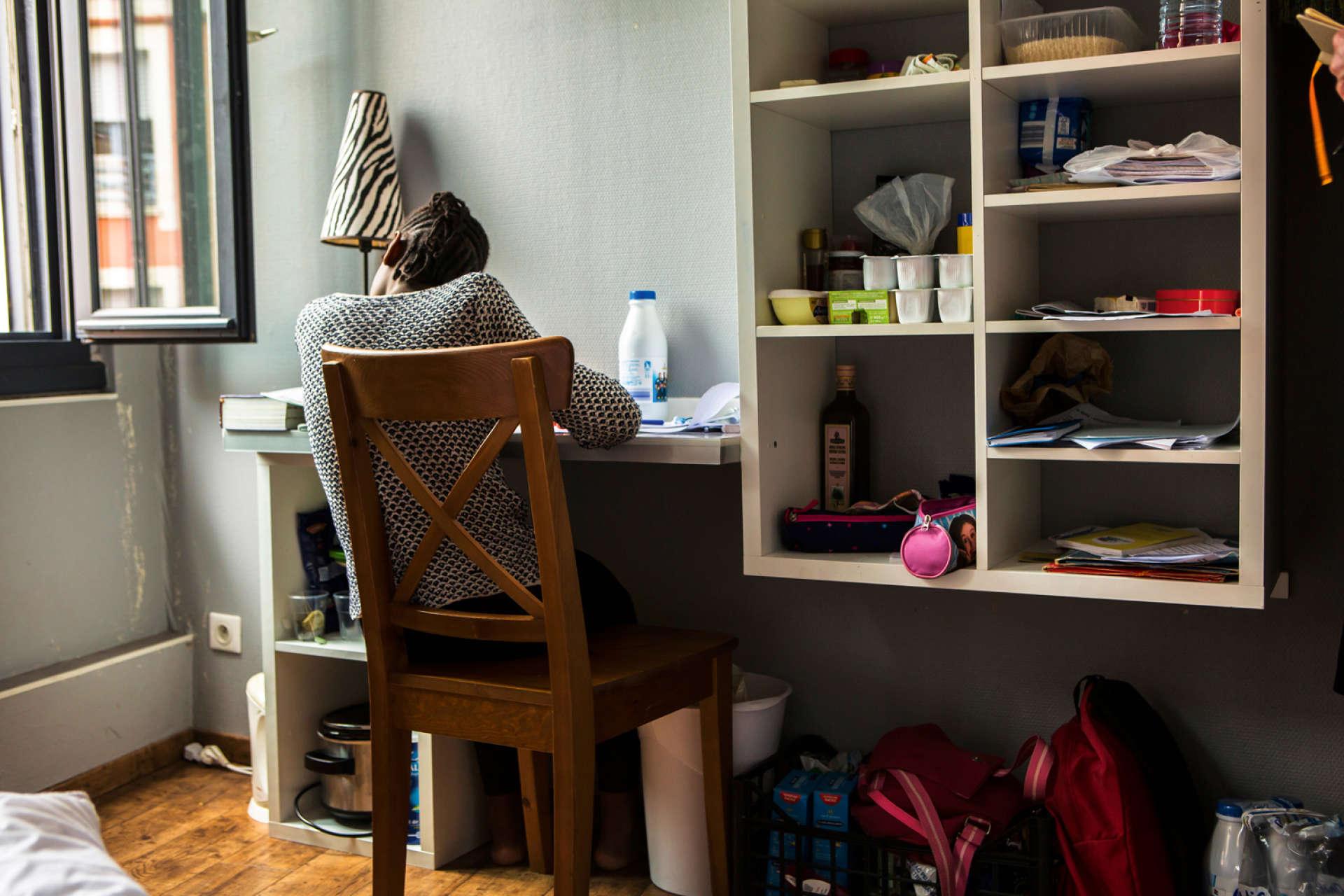 Julienne, la fille de Marie, fait ses devoirs dans la chambre où elle est confinée avec sa mère.