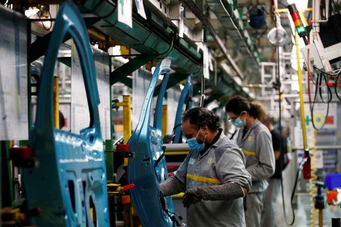 Des employés de l'usine Renault de Flinstravaillent sur la chaîne de montage automobile, le 6 mai.