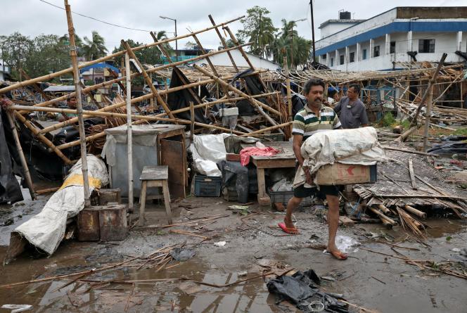 Un homme récupère des affaires dans les débris d'un magasin détruit par le cyclone Amphan, jeudi 21 mai, dans l'Etat indien du Bengale-Occidental.