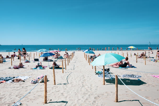 """Plage du Couchant, la Grande-Motte (Hérault), le 21 mai. Premier jour d'ouverture du dispositif unique en France de """"plage organisée"""", permettant aux plagistes de se baigner et de rester sur le sable à l'intérieur d'un emplacement individuel délimité à l'aide de piquets. 75 emplacements sont installés pouvant accueillir 250 personnes par demi-journée. L'accès à la plage est gratuit et se fait après réservation sur le site Internet de l'office du tourisme. Deux de ses salariés ainsi que trois agents de sécurité assurent la vérification des réservations, l'attribution des places et la surveillance du site. Des allées montantes et descendantes à sens unique ont été aménagées pour éviter les croisements. Ce matin, environ 150 personnes ont fréquenté la plage."""