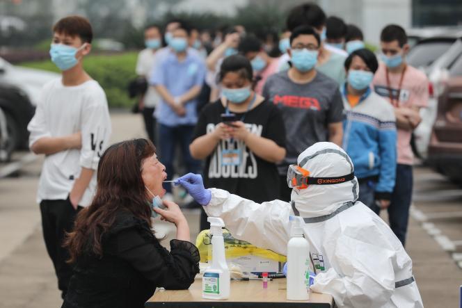 Un travailleur médical prélève un échantillon d'un employé de l'usine de moniteurs AOC pour tester le coronavirus COVID-19 à Wuhan, Chine, le 15 mai 2020.