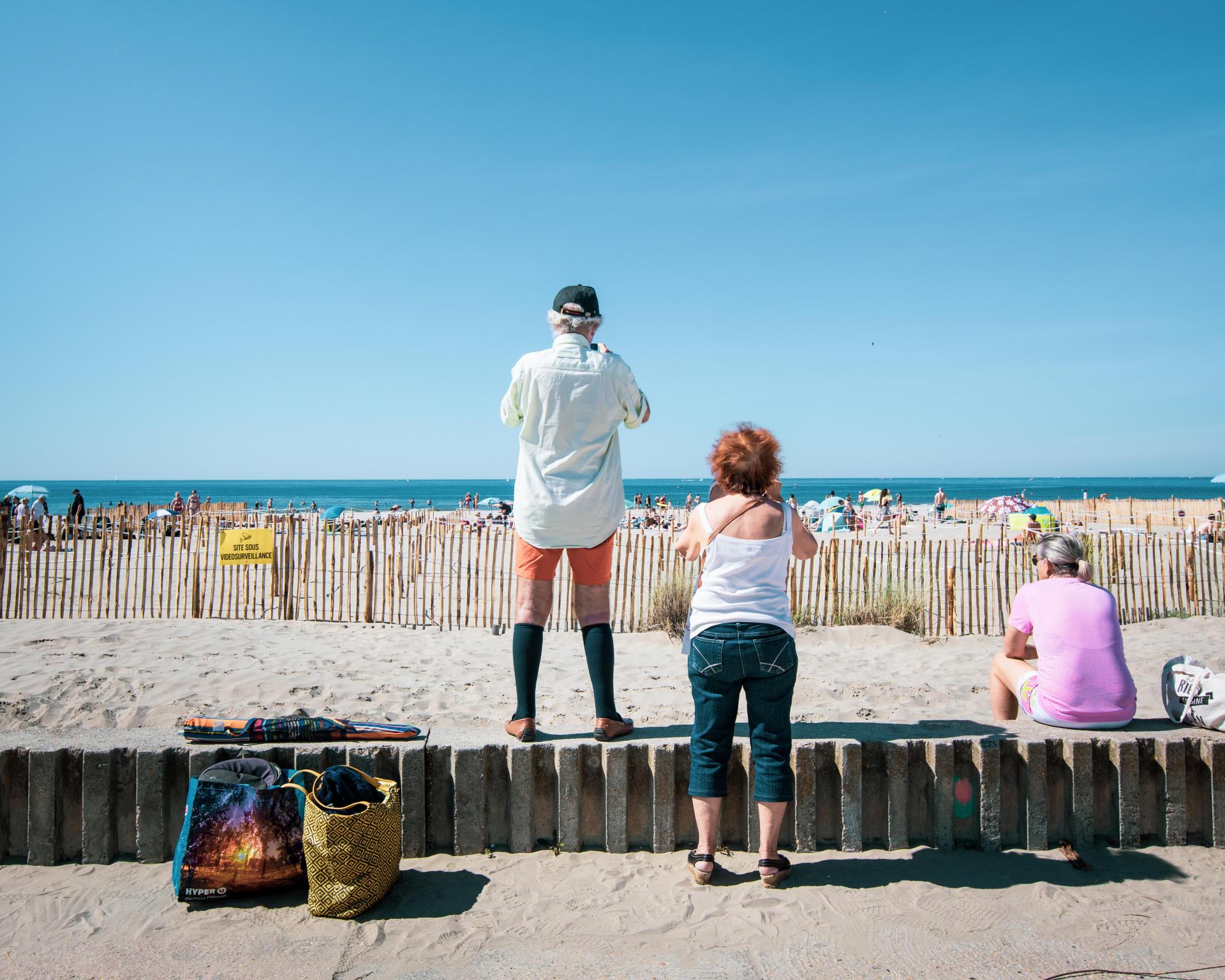 Des passants photographient la plage du Couchant le jour de sa réouverture, le 21mai.