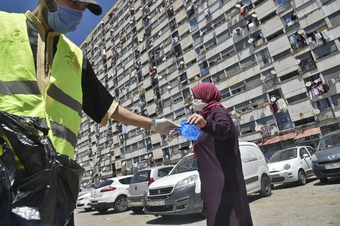 Un bénévole distribue des masques, à Alger, le 21 mai.