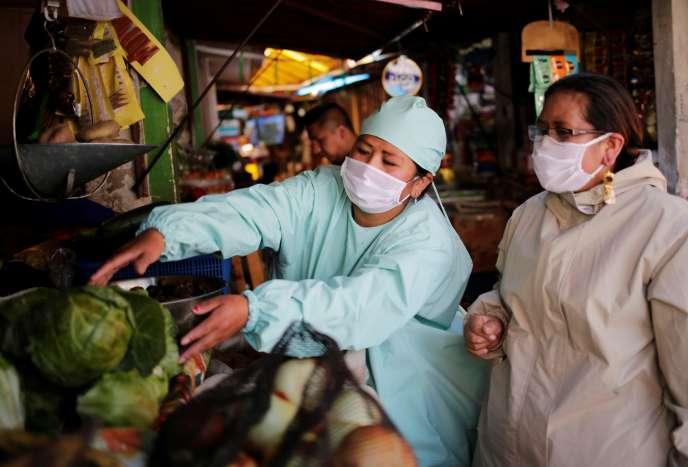 A La Paz, en Bolivie, les vendeurs des marchés portent des masques et des tenues deprotection, le 20 mai.