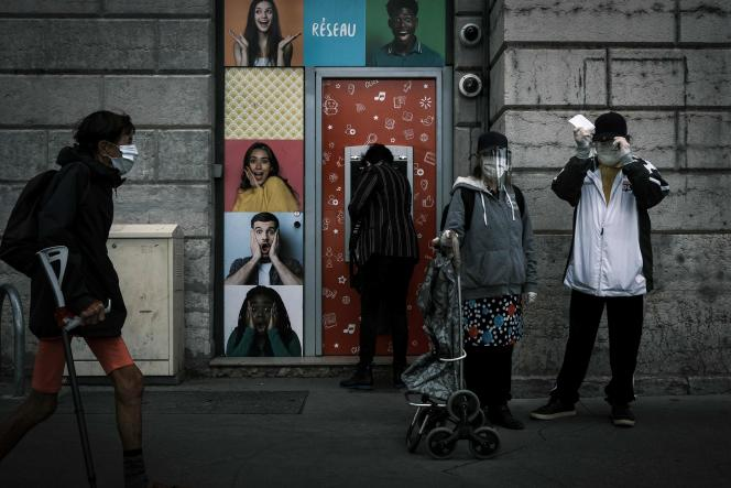 Devant un distributeur de billets lors du premier jour de déconfinement,à Lyon, le 11 mai.