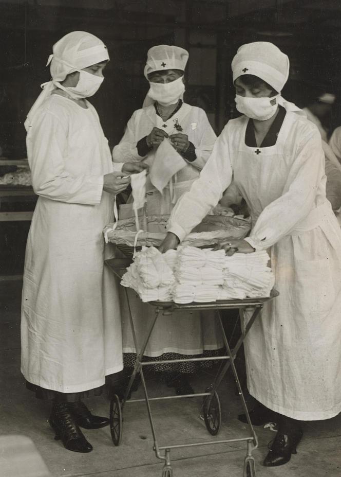 Personnel de la Croix-Rouge réassemblant des masques après stérilisation lors de la pandémie de grippe espagnole, à Boston, en mars 1919.