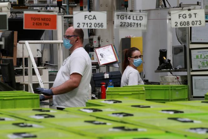 Deux employés masqués dans une usine de Valeo, à Etaples, lors d'une visite d'Emmanuel Macron le 26 mai.