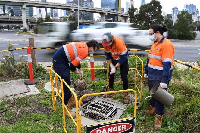 Une équipe d'hydrographes prélève des échantillons d'eaux usées, dans un égoût à Melbourne (Australie), le 19 mai.