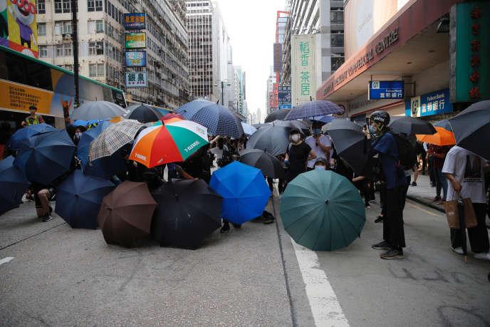 Des manifestants se protègent avec des parapuies dans le centre de Hongkong, mercredi 27 mai.