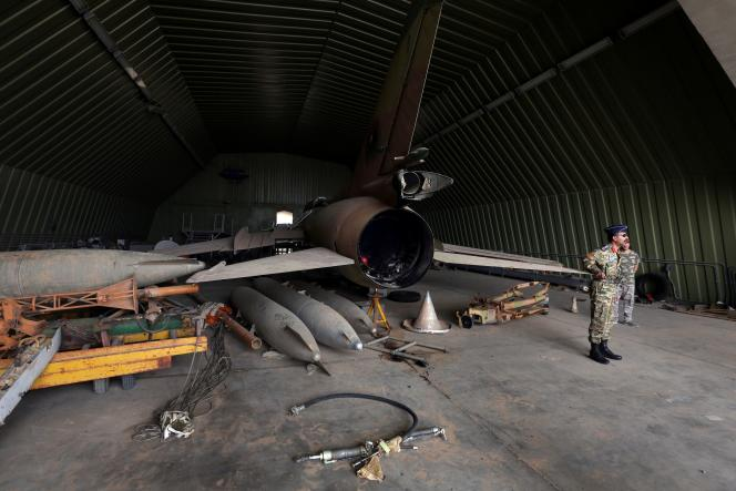 Des membres du gouvernement du GAN de Sarraj, reconnu internationalement, autour d'un Mig-23, après la prise de contrôleaux forces dumaréchal Haftar de la base aérienne de Watiya au sud-ouest de Tripoli, le 18 mai.