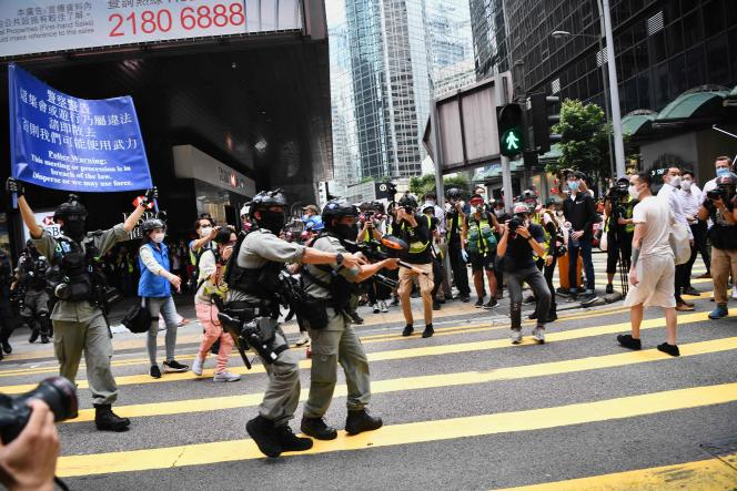 La police antiémeute demande à la foule de se disperser avant de faire usage de la force, dans les rues de Hongkong, mercredi27mai.
