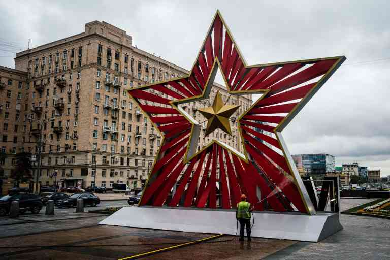 A municipal worker cleans and disinfects an area near an installation dedicated to the 75th anniversary of the victory over Nazi Germany during World War II, by the Triumphal Arch, which commemorates Russia's victory over Napoleon in 1812, on Kutuzovsky Avenue in Moscow on May 8, 2020. Russia will hold only muted celebrations on May 9 for the 75th anniversary of the end of World War II after President Vladimir Putin postponed a Red Square parade due to the coronavirus pandemic. / AFP / Dimitar DILKOFF