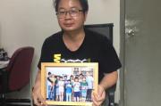 Jiang Nengjie tient dans ses mains la photo des enfants du Hunan auxquels il a consacré un documentaire, chez lui à Canton, le 16 mai.