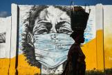 Une femme passe devant une peinture murale incitant au port du masque, à Dar es-Salaam, en Tanzanie, le 26mai 2020.