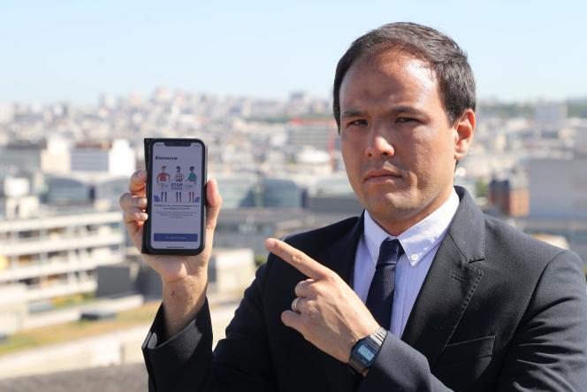 Cédric O pose avec un smartphone équipé de l'application StopCovid vendredi 29 mai, sur le toit du ministère de l'économie.