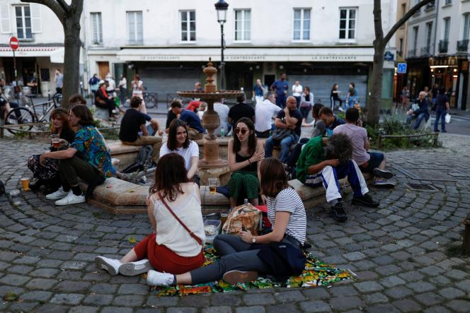 Des groupes de Parisiens assis par terre devant un restaurant fermé de la place de la Contrescarpe à Paris, samedi 30 mai 2020.
