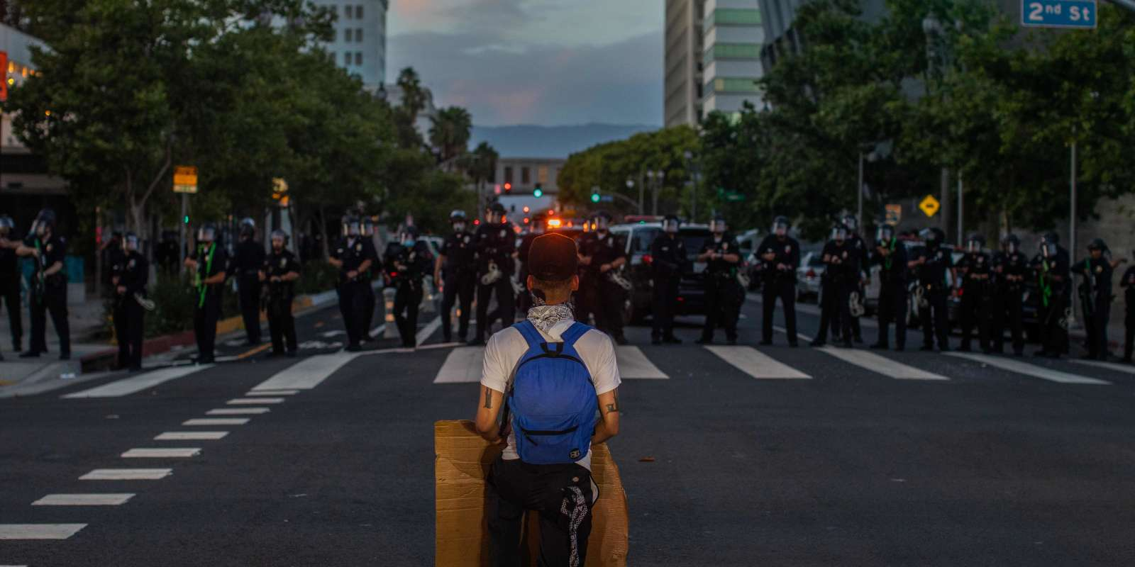 TOPSHOT - A demonstrator kneels in front of a Police line in Downtown Los Angeles on May 30, 2020 during a protest against the death of George Floyd, an unarmed black man who died while while being arrested and pinned to the ground by the knee of a Minneapolis police officer. Clashes broke out and major cities imposed curfews as America began another night of unrest Saturday with angry demonstrators ignoring warnings from President Donald Trump that his government would stop violent protests over police brutality