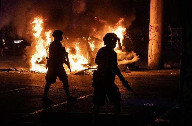 La police monte la garde alors que les pompiers d'Austin (Texas) éteignent une voiture en feu, sous l'autoroute Interstate35, samedi 30mai 2020.