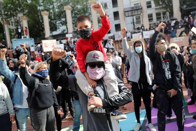 Venu de Vancouver (Washington), Bryan Anaya porte son fils Julian lors d'un rassemblement à la mémoire deGeorge Floyd, à Portland (Oregon), le 31mai 2020.