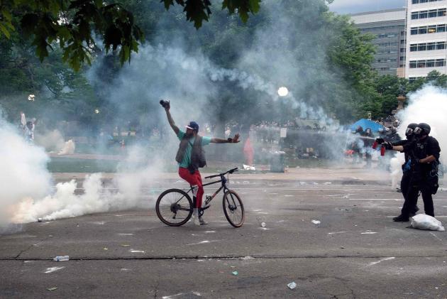 La police vaporise du gaz au poivre sur un manifestant, lors d'une manifestation à Denver (Colorado), le 30mai 2020.La ville a imposé un couvre-feu à partir de samedi soir et le gouverneur, Jared Polis, a appelé la garde nationale après deux nuits de manifestation qui ont ravagé la ville.