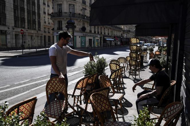 Les gérants d'un restaurant préparent leur terrasse, rue du Quatre-Septembre, à Paris, le 31mai.