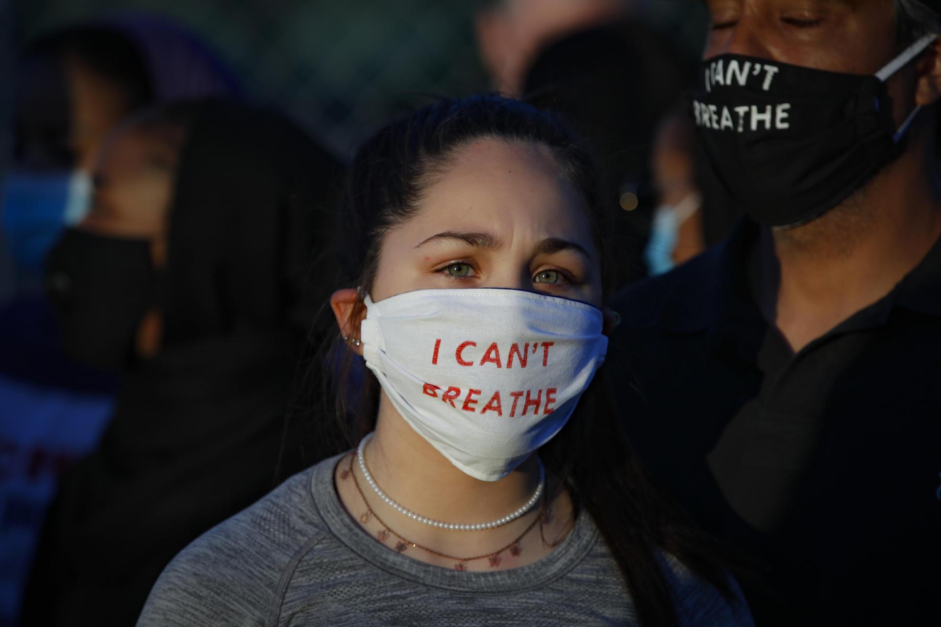 Madeline Curry assiste à une manifestation avec son père, à l'extérieur d'uncommissariat de police de Minneapolis, le 30mai 2020. Sur son masque, on peut lire les derniers mots de George Floyd: «I can't breathe» («je ne peux pas respirer»)