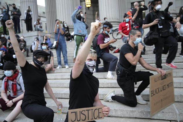 A New York, des manifestants se sont rassemblés, genou à terre en hommage à George Floyd, sur les marches du palais de justice de Foley Square, dimanche 31mai 2020.