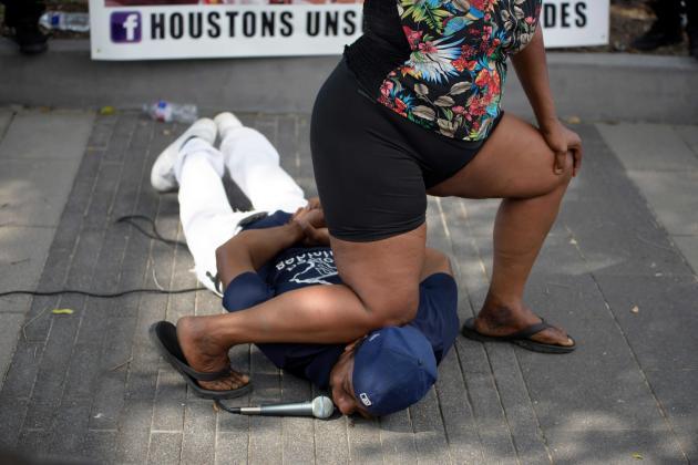 A Houston, au Texas, un homme s'adresse à la foule,pendant qu'une femme montre comment s'est dérouléel'arrestation de George Floyd par Derek Chauvin, le policier mis en cause,lors d'un événement «Justice for George Floyd», le 30 mai 2020.