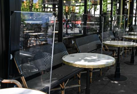 TOPSHOT - Plexiglas separations are seen between tables at a cafe's terrace, on June 1, 2020 in Paris, as France eases lockdown mesures taken to curb the spread of the Covid-19 pandemic (novel coronavirus). cafes and restaurants in green areas of France are authorized to reopen from June 2, 2020 with strict health rules, after weeks of forced closure due to the measures adopted to curb the spread of the COVID-19 pandemic due to the novel coronavirus. / AFP / BERTRAND GUAY