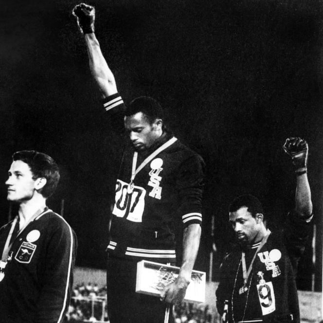 Tommie Smith (au centre) et John Carlos (à droite)aux Jeux olympiques de Mexico, en 1968, sur le podium du 200 mètres messieurs.