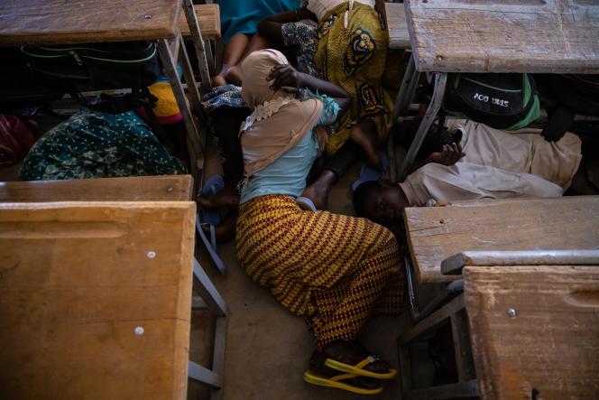 Une écolière de Dori (Burkina Faso) se protège lors d'une simulation d'attaque, le 3 février. Depuis plusieurs mois, le pays est en proie à de nombreux assauts d'organisations terroristes.
