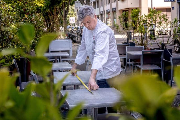 Olivier Paget, chef du restaurant L'Ame Sœur, mesure l'espacement entre les tables pour s'assurer qu'il respecte la norme,à Lyon, le 1er juin.
