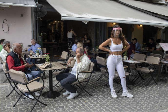 Une serveuse d'un café-restaurant du quartier de Monastiraki, équipée de matériel de protection contre le coronavirus, à Athènes, le 25 mai.