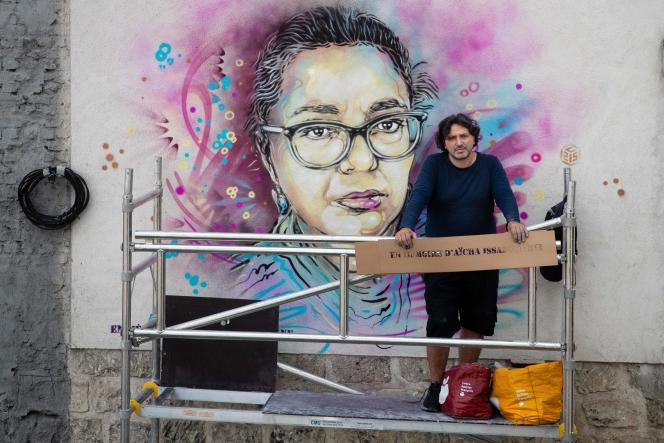 Le street-artiste Christian Guémy (C215) devant sa fresque réalisée le 3 juin à Saint-Ouen « En mémoire d'Aïcha Issadounène » , la caissière de supermarché décédée du Covid-19 le 26 mars.