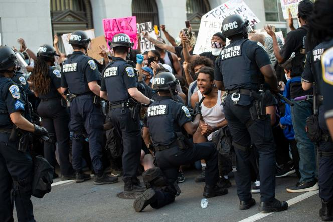Un policier s'agenouille devant la foule venue dénoncer les circonstances de la mort de George Floyd, près de la Maison Blanche à Washington, le 31 mai.