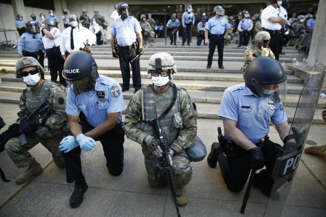 Des membres des forces de l'ordre posent un genou à terre, à Philadelphie, le 1er juin.