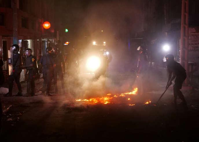 La police anti-émeute tente d'éteindre un feu lors d'une manifestation contre le couvre-feu imposé à cause de la pandémie de Covid-19, à Dakar, le 4 juin 2020.