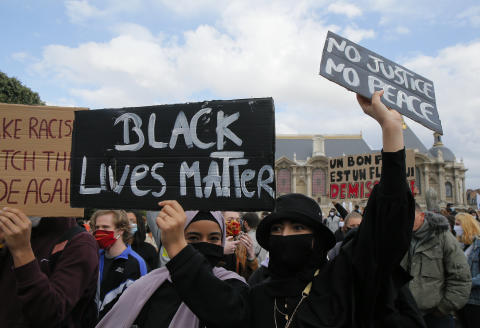 Protesters hold posters an anti-racism demonstration, Thursday, June 4, 2020 in Lille, northern France, where people rallied in homage to George Floyd and to Adama Traore, a French black man who died in police custody. (AP Photo/Michel Spingler)