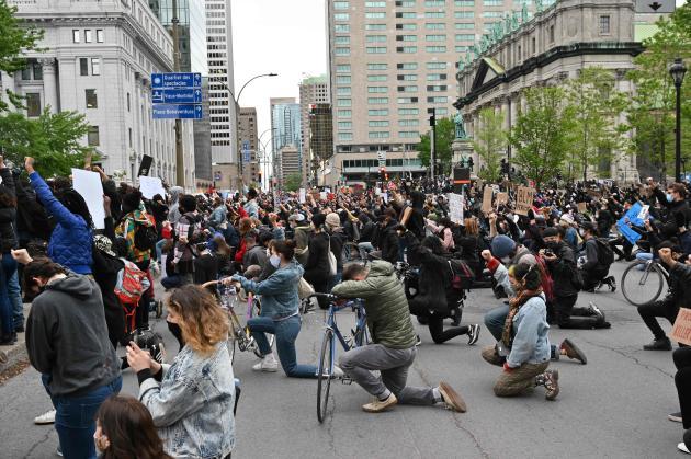 La foule s'agenouille alors qu'elle observe une minute de silence à la mémoire de George Floyd sur la place du Canada, à Montréal, le 31 mai.