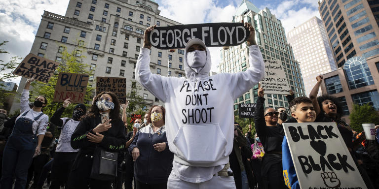 A man holds a skateboard bearing George Floyd's name above his head as thousands of people gather for a peaceful demonstration in support of Floyd and Regis Korchinski-Paquet and protest against racism, injustice and police brutality, in Vancouver, on Sunday, May 31, 2020. (Darryl Dyck/The Canadian Press via AP)