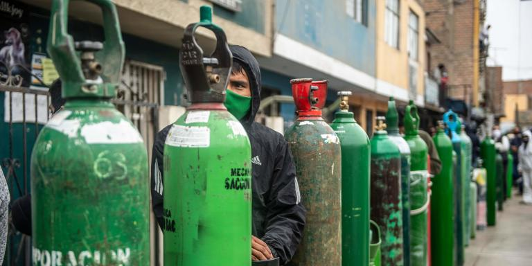 TOPSHOT - People queue to refill their empty oxygen cylinders in Callao, Peru, on June 3, 2020 amid the COVID-19 coronavirus pandemic. Relatives of people with COVID-19 are desperate for oxygen to keep their loves ones alive in Peru, where patients have been dying for lack of oxygen. / AFP / Ernesto BENAVIDES
