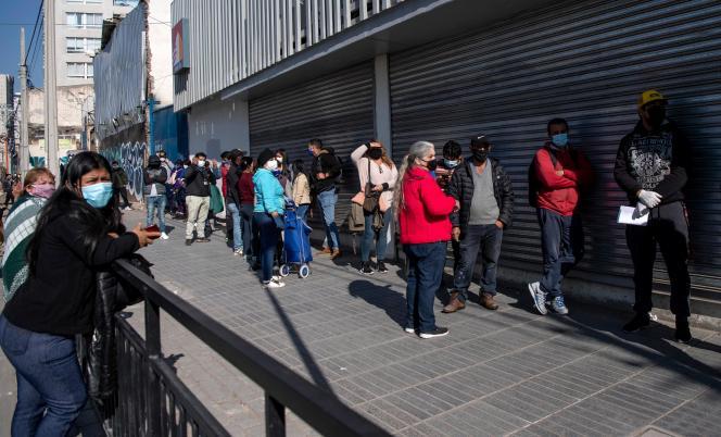 Des gens équipés de masques font la queue pour entrer dans une banque d'Etat à Santiago, au Chili, le 5 juin 2020, pays où les morts dues au Covid-19 ont augmenté de plus de 50% au cours de la semaine, a annoncé vendredi le ministère de la santé.